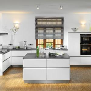Białe meble kuchenne pięknie prezentują się zwieńczone szarym blatem. Tutaj powierzchnia robocza koresponduje z barwą korpusu wyspy kuchennej. Fot. Brigitte.
