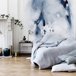 Na ścianie za łóżkiem umieszczono pastelową dekorację w niebieskich odcieniach, która przyjemnie ożywia przestrzeń. Fot. Broste Copenhagen.