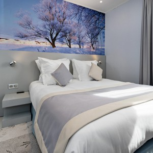 Zimowy pejzaż w błękitnych odcieniach umieszczony nad łóżkiem doskonale prezentuje się w sypialni. Fot. Le jardin de Montmarte Hotel.