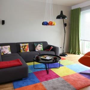 Radosny ton całej aranżacji bez wątpienia nadaje kolorowy dywan. Efekt dopełnia wielobarwne oświetlenie oraz fotel. Projekt: Dorota Szafrańska. Fot. Bartosz Jarosz.