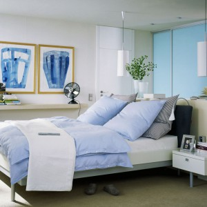 Błękitne fronty szafy przesuwnej doskonale komponują się z pozostałymi, jasnymi ścianami. Tkaniny oraz dekoracje w niebieskiej kolorystyce dodają sypialni charakteru. Fot. Raumpuls.