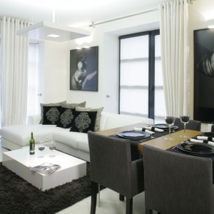 Nowoczesne, czarno-białe wnętrze urządzone wpisuje się w kanony minimalizmu. Zmysłowy charakter nadają mu akty, zdobiące ścianę za sofą narożną oraz przy stole. Projekt: Julita Chrząstek. Fot. Monika Filipiuk-Obałek.