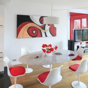Nowoczesna grafika na ścianie zdradza sympatię właścicieli do nowoczesnej sztuki, jak również podkreśla oryginalny wygląd wnętrza. Dekoracja koresponduje kolorystycznie ze ścianą telewizyjna i poduszkami w jadalni. Projekt: Michał Mikołajczak. Fot. Monika Filipiuk-Obałek.