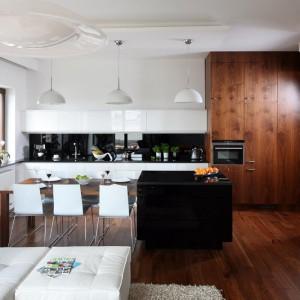 W otwartej strefie dziennej całą zabudowę kuchenną ulokowano na jednej ścianie, tak iż rozciąga się ona aż do przedpokoju. Przestronna wyspa połączona z praktycznym stołem oddziela ją od salonu. Projekt: Agnieszka Ludwinowska. Fot. Bartosz Jarosz.