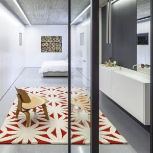 Kolorystycznym akcentem w przeważającej mierze szarych wnętrzach są czerwone detale. W przestrzeni master bedroom jest to wzorzysty biało-czerwony dywan i efektowne, vintage'owe pokrętła armatury łazienkowej. Projekt: Pitsou Kedem Architects. Fot. Amit Geron.