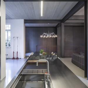 Nowoczesna kuchnia została ubrana w stalową szatę. Stalowy jest tutaj blat wyspy kuchennej, wpuszczony w niego zlewozmywak, towarzysząca mu bateria, a nawet wysoka zabudowa kuchenna. Projekt: Pitsou Kedem Architects. Fot. Amit Geron.