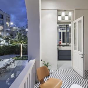 Duży, otwary balkon zachwyca jasnymi kolorami, posadzką-szachownicą i półkolami konstrukcji budynku. Razem z sąsiadującym tarasem, stanowi prywatny azyl, odgradzający mieszkanie od miejskiego zgiełku. Projekt: Pitsou Kedem Architects. Fot. Amit Geron.
