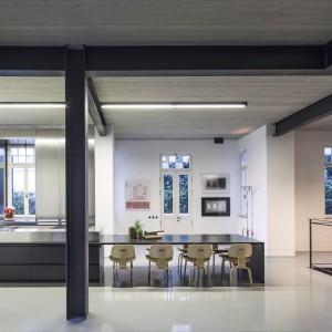 Blat dużej wyspy kuchennej przedłożono i wyprofilowano tak, aby stworzyć stół jadalniany. Posiłek przy nim zjeść może aż 8 osób. Projekt: Pitsou Kedem Architects. Fot. Amit Geron.