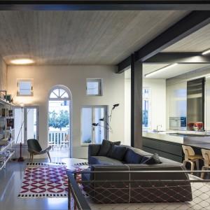 Ciemnoszare, wyeksponowane belki stropowe i filary, betonowe i stalowe powierzchnie, a także pomalowana na czerwono metalowa siatka na poręczach schodów - wszystkie te elementy budują we wnętrzu industrialny klimat. Jego surowość przełamuje przytulny narożnik i wzorzysty dywan. Projekt: Pitsou Kedem Architects. Fot. Amit Geron.