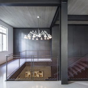Nad schodami zawsił oryginalny żyrandol-pająk, z licznymi ramionami, zwieńczonymi lampkami w loftowym stylu. Jego biała barwa sprawia, że szczególnie przyciąga wzrok na tle ciemnoszarej ściany. Projekt: Pitsou Kedem Architects. Fot. Amit Geron.