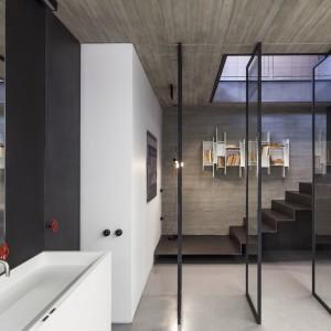 We wnętrzu królują geometryczne formy i proste linie. Prostokątne, przeszklone ekrany, oddzielające przestrzeń łazienki od holu, dywanowe schody i naścienna półka - wszystkie te elementy są różnymi interpretacjami geometrycznych form. Projekt: Pitsou Kedem Architects. Fot. Amit Geron.