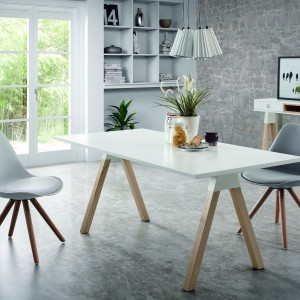 Stół Stick to efektowne połączenie białego blatu i drewnianych nóg, układających się w oryginalne kształty dwóch liter V. Harmonizują stylistyką z eamewoskimi krzesłami i nowoczesnym wystrojem jadalni. Fot. La Forma/Le Pukka.