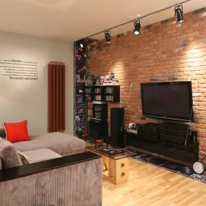 Urządzony w stylu loft apartament zdobią szarości oraz ceglana ściana. Całość ociepla drewno: drewniana podłoga przełamuje chłód aranżacji. Projekt: Iza Szewc. Fot. Bartosz Jarosz.