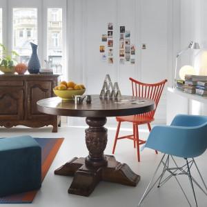 Stół z kolekcji Olden Days to piękno klasyki, wykonanej w drewnie. Gruba, zdobna noga podtrzymuje zaokrąglony blat i nadaje charakter całemu wnętrzu. Klasyczne meble ciekawie komponują się z nowoczesnymi, kolorowymi krzesłem i pufem. Fot. Ludwik Styl/Domoteka.