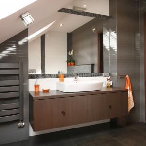 Pomarańczowe akcenty w tej rodzinnej łazience doskonale spełniły swoje zadanie. Doskonale ożywiają stonowane wnętrze. Jeśli ten kolor nam się znudzi to szybko można wymienić go na inny. Projekt: Marta Kilan. Fot. Bartosz Jarosz.