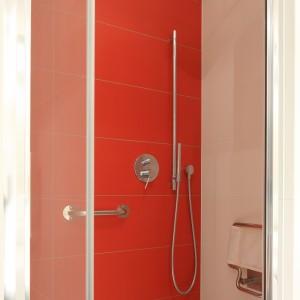 Ścianę za prysznicem wykończono czerwonymi płytkami, dzieli czemu prysznic wyróżnia się na tle aranżacji w bieli. Projekt: Małgorzata Galewska. Fot. Bartosz Jarosz.