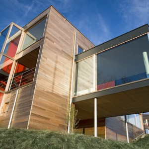 Postrzegane jako tradycyjny materiał pasujący do wiejskich chatek, drewno zaskakuje jako materiał elewacyjny nowoczesnej, geometrycznej bryły domu. W połączeniu z prostymi formami i dużymi przeszkleniami prezentuje się bardzo efektownie. Fot. DLH.