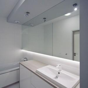 W łazience króluje biel, zamknięta w proste, minimalistyczne formy. Duże lustro pozbawione ramy, kubistyczna umywalka i gładkie fronty - wszystkie elementy są pochwałą minimalizmu. Fot. RED Real Estate Development.