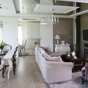 Wytworny salon z jadalnią to pomysłowo urządzona przestrzeń w stylu glamour. Obie strefy oddziela gustowna kanapa w kolorze jaśniejszym od reszty wyposażenia salonu. Projekt: Agnieszka Hajdas-Obajtek. Fot. Bartosz Jarosz.