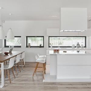 Piękna i modna biała kuchnia ze sporych rozmiarów wyspą kuchenną. Duży praktyczny mebel pełni funkcję domowego baru i powierzchni gotowania. Fot. Atlas Kuchnie, kuchnia Patrycja Listwowa.
