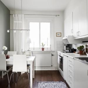 W niewielkiej kuchni postawiono na zabudowę jednorzędową, dzięki czemu udało się również wpasować nieduży stół jadalniany, elegancko schowany za lodówką. Dominująca we wnętrzu biel sprawiła, że pomieszczenie wydaje się znacznie większe niż jest w rzeczywistości. Fot. Stadshem.se/Janne Olander.