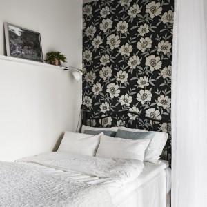 W przestrzeni salonu, we wnęce za zasłoną schowano łóżko. Przestrzeń sypialni wyodrębniono za pomocą kwiecistej tapety na ścianie za wezgłowiem. Fot. Stadshem.se/Janne Olander.