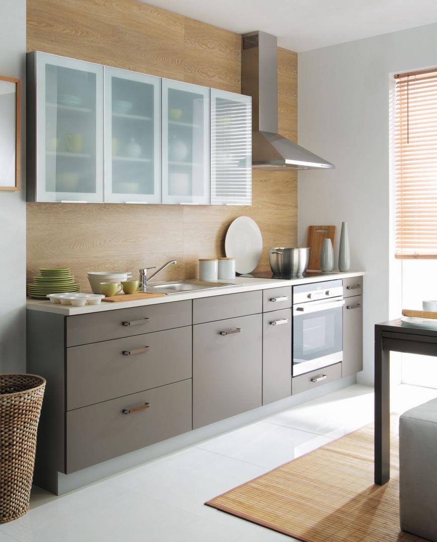 """Prosty układ i nowoczesne, minimalistyczne wzornictwo potęgują wrażenie przestronności, mimo że kuchnia ma jedynie 5 m2. Umieszczenie mebli w jednej linii, zgodnie z zasadą """"mniej znaczy więcej"""", daje więcej przestrzeni na środku pomieszczenia. Można tu postawić stół, bądź zamontować małą kuchenną wyspę. Fot. Black Red White, kuchnia Tabes."""