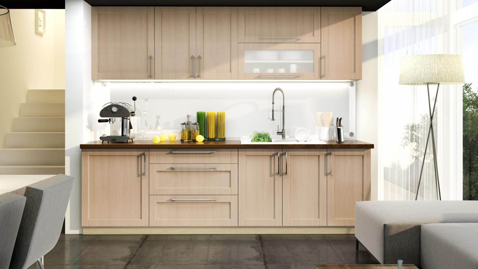 Zabudowa na jedną ścianę pozwoliła wpasować kuchnię w miejsce pomiędzy salonem a klatką schodową. Wysokie szafki górne, poprowadzone pod sam sufit wykorzystują maksimum dostępnej przestrzeni. Fot. Stolkar, model Karolina.