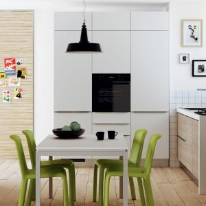 Oryginalnie potraktowana przestrzeń kuchni, włączonej w strefę dzienną. Powierzchnię roboczą zaplanowano pod oknem, mieszcząc na krótkim blacie o długości zaledwie 2,2 metra zlewozmywak i płytę grzewczą. Wszelkie schowki przeniesiono na prostopadłą ścianę i ukryto w wysokiej, białej zabudowie, utrzymanej w minimalistycznym stylu, wizualnie stapiającej się ze ścianą. Fot. Scavolini.