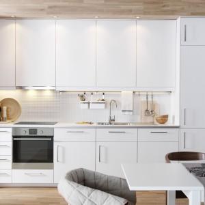 Białe meble kuchenne i jasna ściana nad blatem powiększają wizualnie przestrzeń, odbijając padające na powierzchnie światło. Wpasowanie aneksu we wnękę sprawia, że zajmuje on niewiele miejsca. Wysoka zabudowa górna pozwala maksymalnie wykorzystać przestrzeń, a także utrzymać porządek na blacie. Fot. IKEA.
