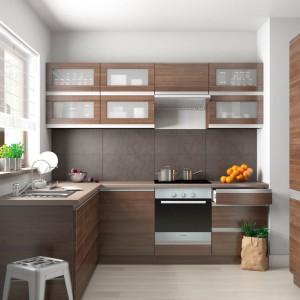 Propozycja Castoramy do niewielkich wnętrz. Zabudowa w kształcie litery L wykorzystuje przestrzeń w tej zamkniętej kuchni. Górne szafki z przeszklonymi frontami nadają lekkość nieco ciężkiemu kolorowi drewna. Fot. Castorama, kuchnia Malibu.