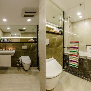 Elegancka łazienka została utrzymana, podobnie jak całe wnętrze, w kolorach ziemi. Płytki imitujące kamień, lekkie przeszklenie pozwalające wziąć wygodny prysznic w wannie oraz proste lustro bez ram, nadają jej delikatny i elegancki wyraz. Projekt i zdjęcia: Archlin Studio.