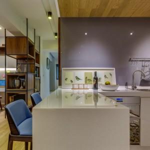 Częściowo zamkniętą kuchnię oddziela od ciągu komunikacyjnego niewielki półwysep, zaadaptowany na dwuosobowy, domowy bar. Projekt i zdjęcia: Archlin Studio.