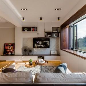 W salonie ciepłe akcenty drewniane tonowane są chłodniejszymi elementami, utrzymanymi w modnych szarościach. Szary kolor odnajdziemy w postaci kanapy, miękkiego dywanu, jak i ściany za telewizorem. Projekt i zdjęcia: Archlin Studio.