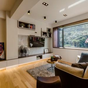 Drewniana podłoga buduje przytulny nastrój w mieszkaniu, a także harmonizuje z ramą okienną i koresponduje z przyrodą za oknem. Projekt i zdjęcia: Archlin Studio.
