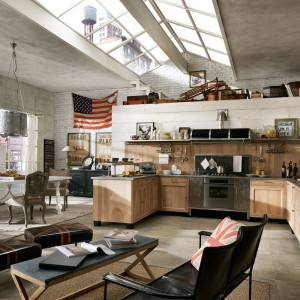 Drewniane meble kuchenne zestawiono ze stalowymi powierzchniami, postarzanymi pufami w salonie i stylizowanymi, barokowymi meblami w jadalni. Eklektyczne wnętrze zachwyca fantazyjną aranżacją. Fot. Marchi Cucine.