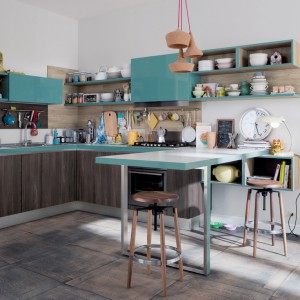 Turkusowe fronty szafek i rama blatu kuchennego w tym samym kolorze, industrialne stołki, okrągły zegar z tarczą oraz stylizowana, biała komoda. Wszystkie te elementy są idealne do kuchni w stylu vintage. Fot. Veneta Cucine, kolekcja Start Time Go.