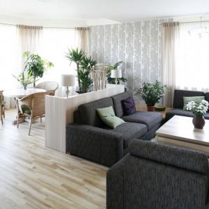 Podział salonu na dwie strefy pozwolił w pomysłowy sposób zagospodarować dużą, otwarą przestrzeń. Dodatkowo przestronności dodają pomieszczeniu duże okna.  Fot. Bartosz Jarosz.