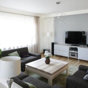 Najbardziej nowoczesnym elementem aranżacji jest ściana telewizyjna. Sprzęt RTV ustawiono na nowoczesnej szafce z lakierowanymi frontami w kolorze złamanej bieli. Fot. Bartosz Jarosz.