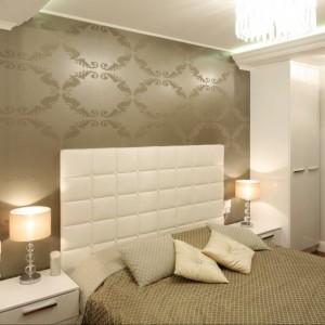 Połyskująca tapeta w stylu glamour stanowi doskonałe tło dla bialego, wysokiego, tapicerowanego zagłówka oraz ozdobnych lamp umieszczonych po obu stronach łóżka. Projekt: Karolina Łuczyńska. Fot.Bartosz Jarosz.