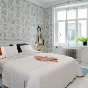 W tej sypialni tapeta zdobi wszystkie ściany. Stonowana kolorystyka dopełnia wnętrze urządzone w skandynawskim stylu. Fot. Alvem Makleri.