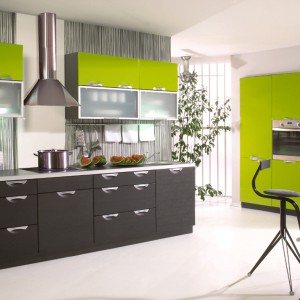 Intensywna, limonkowa zieleń w połysku to idealny sposób na wykończenie frontów mebli kuchennych. Najlepiej jeśli dozować ją będziemy rozsądnie, tonując innymi kolorami, np. ciemnym brązem. Fot. Stolkar, kuchnia Emilia.