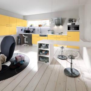 Białe korpusy i blat mebli kuchennych ożywają dzięki żółtym frontom, wpadającym w odcień kurkumy. Fot. Pino, meble z programu PN100.