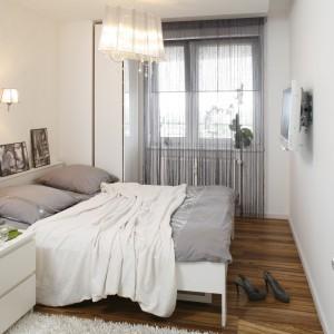 Subtelna aranżacja sypialni skąpanej w bieli i szarości. Telewizor zamontowany na ścianie pełni jedynie rolę praktyczną, prawie nie przykuwając uwagi. Projekt: Małgorzata Mazur. Fot. Bartosz Jarosz.