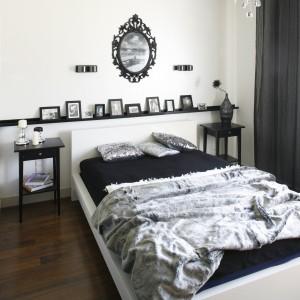 Elegancka i stylowa sypialnia w biało-czarno-szarej tonacji. Wysokie stoliki nocne oraz półka nad łóżkiem wyznaczają stylistykę wnętrza. Projekt: Małgorzata Mazur. Fot. Bartosz Jarosz.
