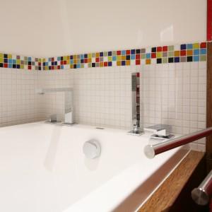 Łazienka o powierzchni 5 m kw. została zaprojektowana dla rodziny. Uniwersalnej aranżacji w bieli ocielonej drewnopodobnymi płytkami wyrazu dodaje kolorowa mozaika. Projekt: Dorota Szafrańska. Fot. Bartosz Jarosz.
