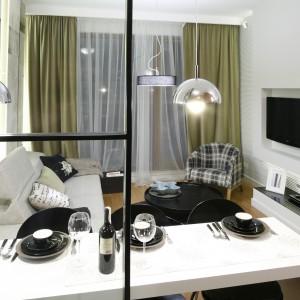 Prosta forma ściany telewizyjnej opiera się na białym, podświetlonym panelu z wnęką, w której umieszczono telewizor. Sprzęt DVD ustawiono na minimalistycznej, niskiej szafce. Projekt: Michał Dudko. Fot. Bartosz Jarosz.