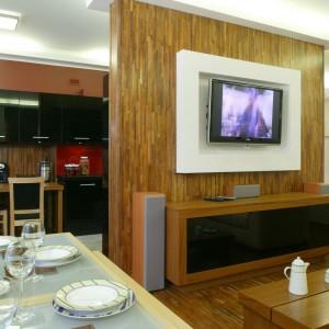 Ściana telewizyjna wykończona fornirem w kolorze drewna to efektowny, ale i praktyczny element salonu. Ulokowana między kuchnią a pokojem dziennym, rozdziela te dwie strefy. Projekt: Norbert Górecki. Fot. Monika Filipiuk-Obałek.
