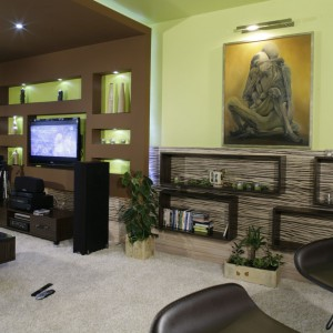 Pomysłowa ściana telewizyjna płynnie przechodzi w sufit podwieszany. Dzięki licznym wnękom można ustawić w niej telewizor oraz wiele dekoracyjnych bibelotów. Projekt: Anna Mormon. Fot. Monika Filipiuk-Obałek.