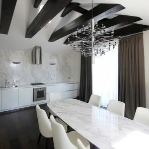 W przestrzeni kuchni i jadalni dominują jasne barwy. Białe meble kuchenne, płytki nad blatem, skórzane krzesła i kamienny stół w jadalni - wszystko utrzymane zostało w jasnych kolorach. Projekt: Ramūnas Manikas, Valdas Kontrimas. Fot. Ramūnas Manikas.